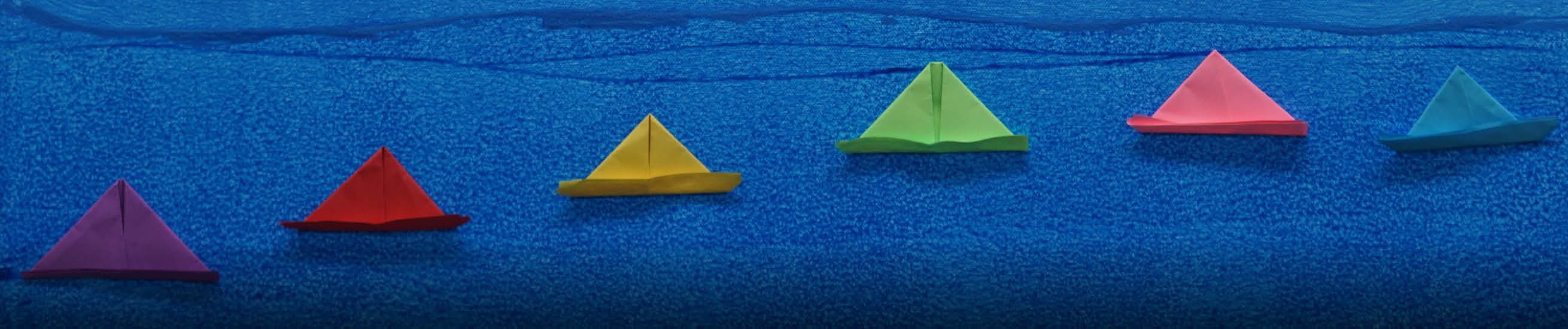 Artwor with blue background and paper boats