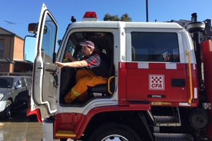 Able client Robert sitting inside a red and white CFA fire truck.