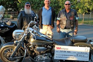 'Fathers' and 'Waffles' of the Ullysses Bike club standing with Edmund McMahon of Able Australia with a large cheque for $1650
