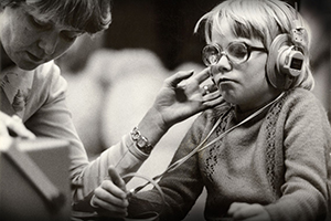 Black and White photo of young boy with glasses and headphones