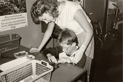 Black and White photo woman with young child reading braille