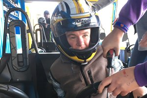 Able client Michael wearing a motorbike helmet being buckled into a go-kart on his holiday.