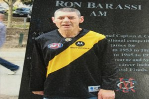 Able client Colin standing in front of a Ron Barassi statue wearing a Richmond Tigers jersey