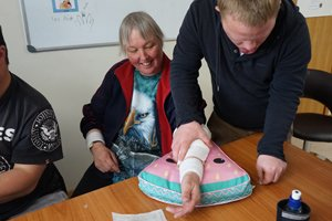 Two Able clients practising First Aid with one wrapping a bandage around the other's arm.