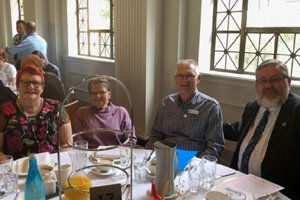 Able volunteer Daryl sitting at a table with three others at the Volunteer of the Year awards