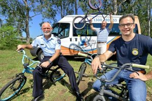 Three men on bikes in front of an Able Australia bus